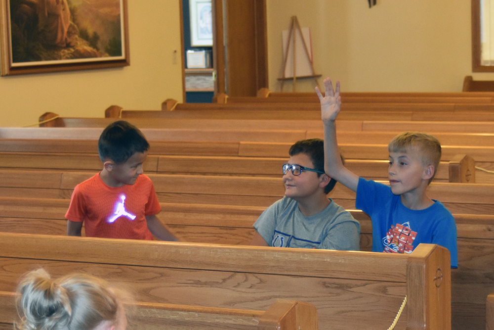 Boys learning with raised hand.
