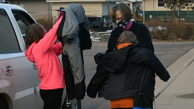 Youth trying on coats.